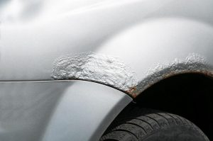 Car with damaged metal with rusty paint and corrosion above the tire